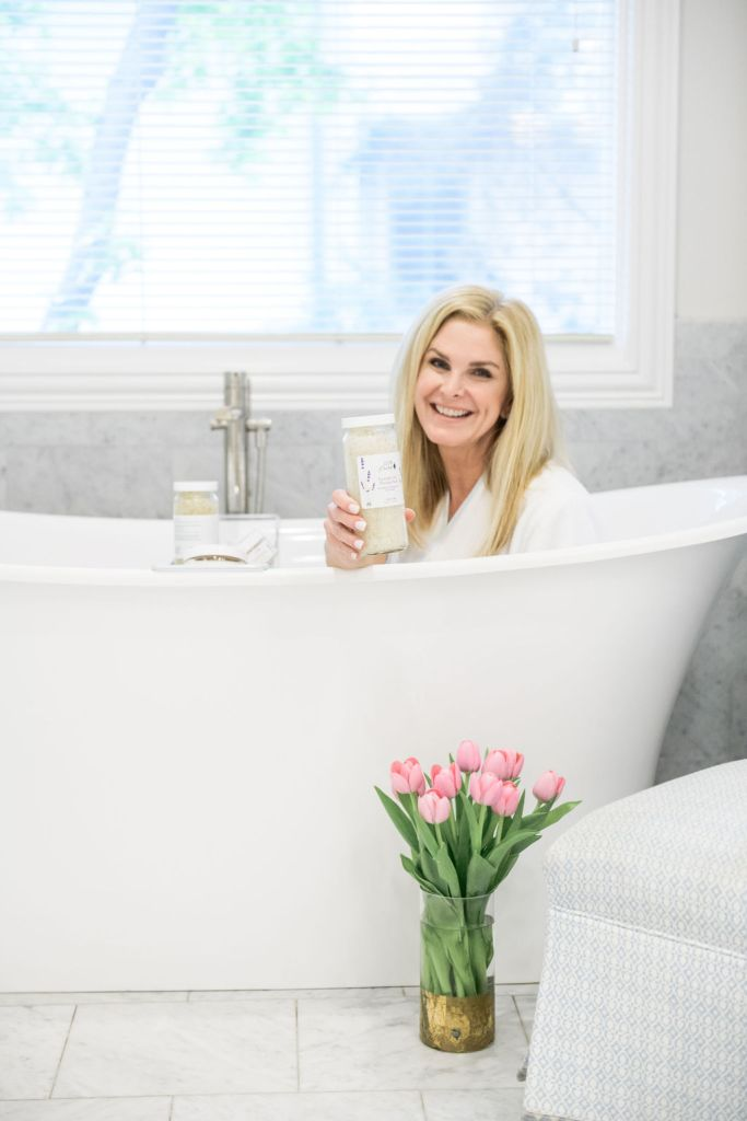 tanya foster in a bath holding 100% pure products