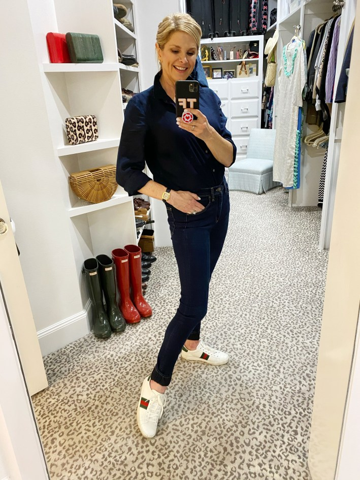 tanya foster in a blue button up blouse jeans and gucci sneakers