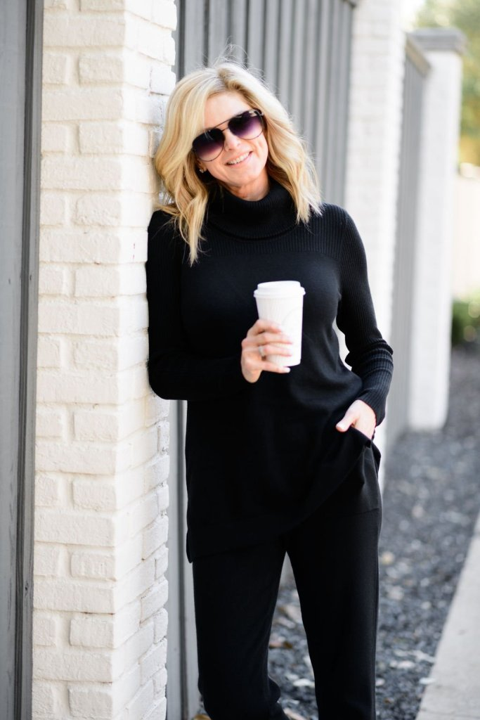 tanya foster in chico's black ribbed turtleneck cotton-cashmere blend joggers and marc fisher hiking boots holding a coffee cup