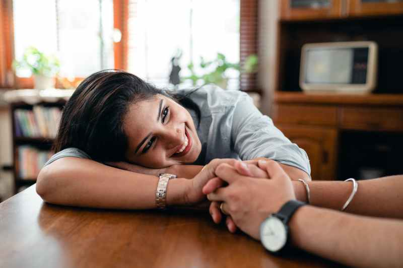 happy ethnic woman sitting at table and smiling while holding hand of husband