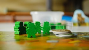 green board game meeples on a table.