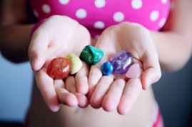 woman holding six polished stones