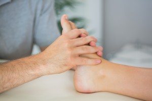 Hands on massage therapy on the plantar surface of the foot.