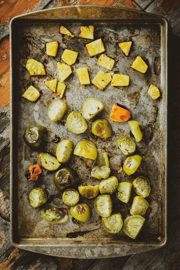 roasted pineapple, habanero, and tomatillos on a baking sheet shot from above