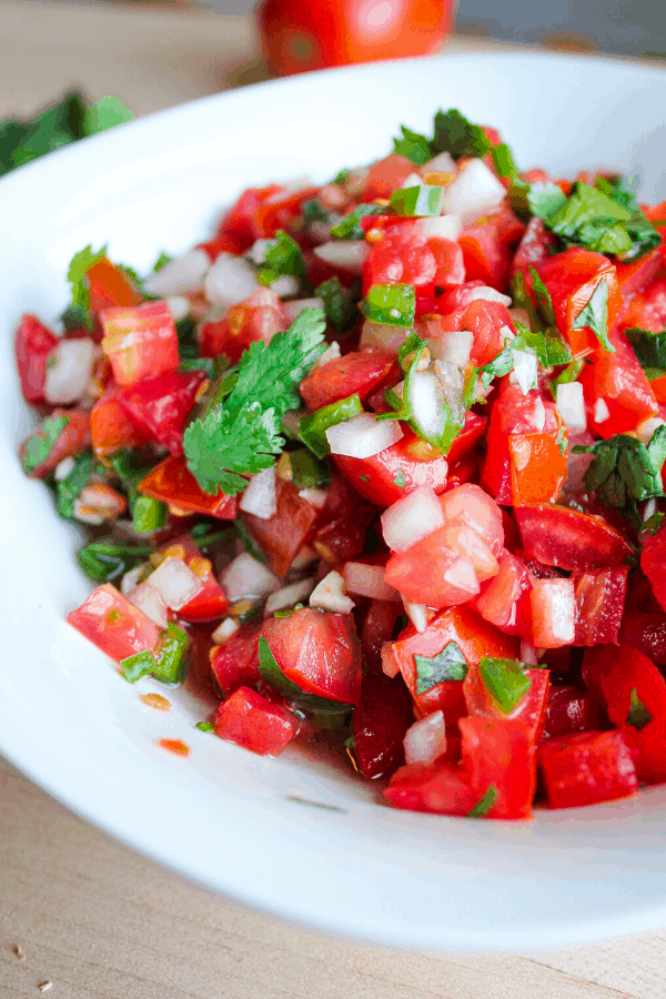 Pico De Gallo in a white bowl on a wood surface with cilantro and tomato in background