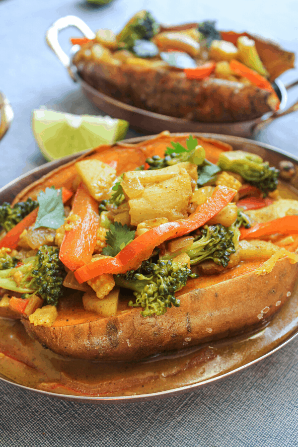 Two stuffed baked sweet potato topped with vegetable coconut curry in copper dish on blue surface with lime wedge