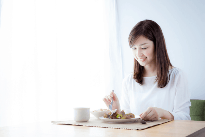 women sitting at table eating alone with smile on face