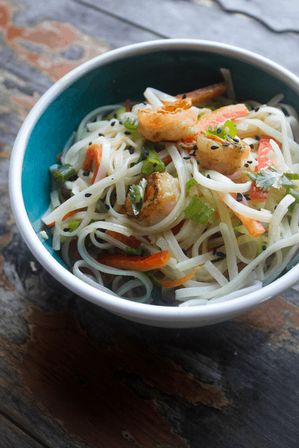 tossed spring roll bowls with shrimp and ginger garlic lime sauce in blue bowl on wood surface