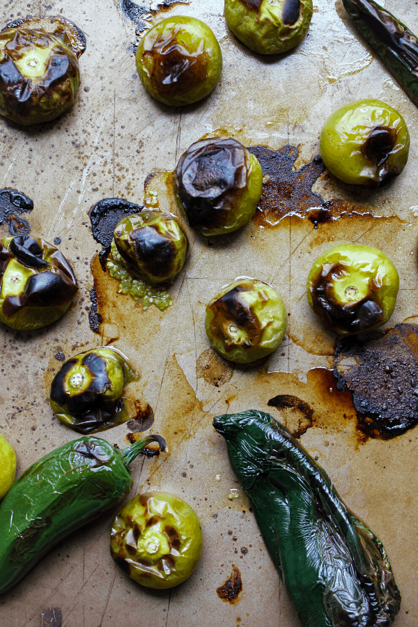 roasted tomatillos and peppers on a baking sheet.