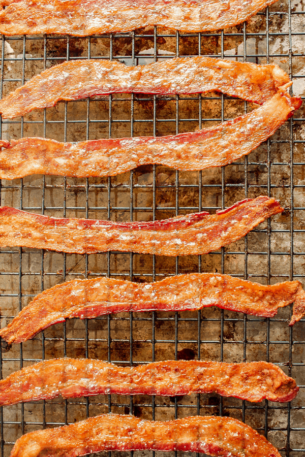 cooked bacon strips on wire cooling atop baking sheet