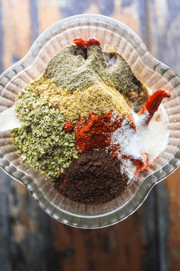 birria produce covered in spices in blender shot from above