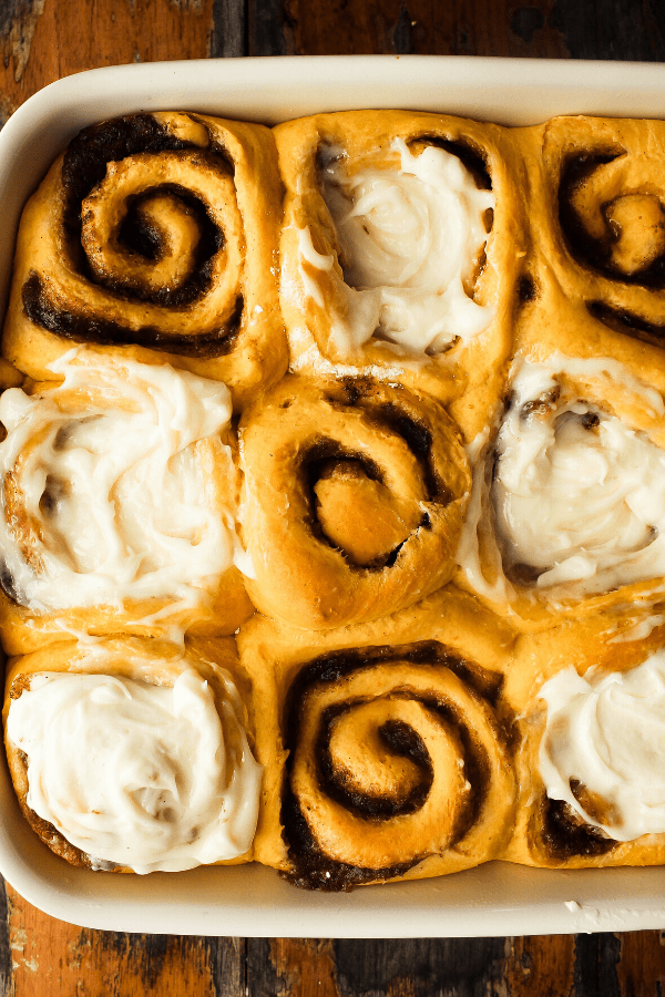 pumpkin cinnamon rolls with chai spice half iced from above in pan