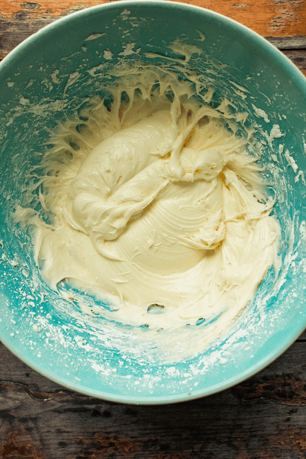 cream cheese icing in blue bowl from above