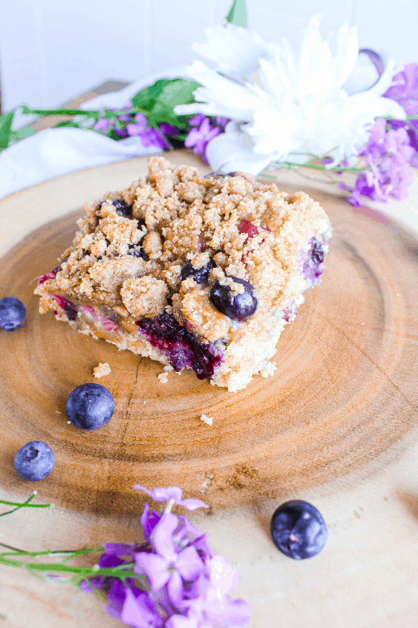 Slice of blueberry rhubarb buckle cake on wood trunk platter with scattered blueberries and flowers.