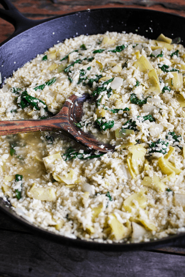 Cast-iron skillet with wooden spoon filled with spinach artichoke casserole minus cheeseprior to baking.