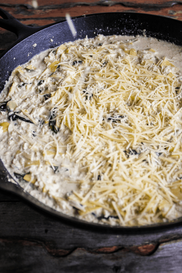 Spinach artichoke casserole prior to baking sprinkled with shredded parmesan cheese in cast-iron skillet.