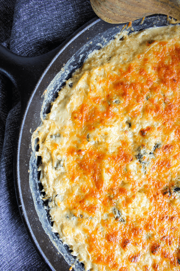 Close-up of half of baked spinach artichoke casserole in cast-iron pan shot from above.
