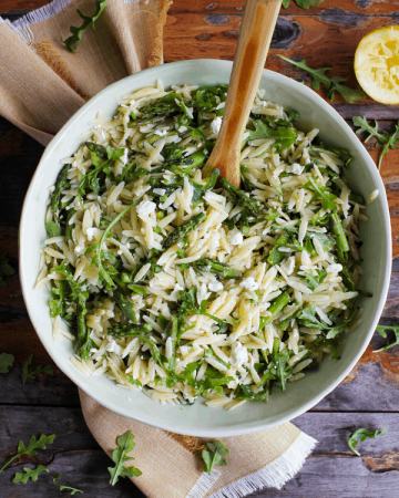 Large bowl of lemon orzo salad with wooden spoon atop a yellow towel with sprinkled arugula and lemon half shot from above.