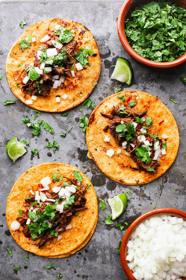 three beef birria tacos laid flat on a sheet pan with sides of cilantro and white onions and scattered lime wedges shot from above