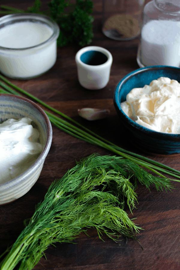 Ingredients for dill ranch on dark wood surface.