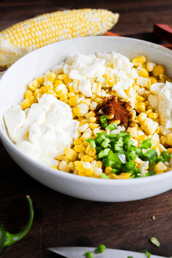 Close up of Mexican street corn ingredients in a bowl with corn cob in background.