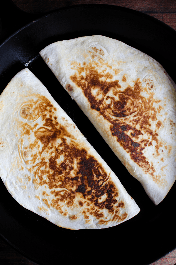 Two grilled quesadillas in a cast-iron skillet shot from above.