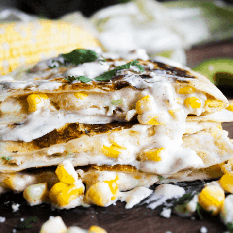 Close up of stacked quesadilla slices drizzled with creamy chipotle sauce with corn cob in background.