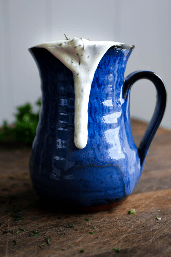 Ranch in blue vase dripping down side with herbs in background.