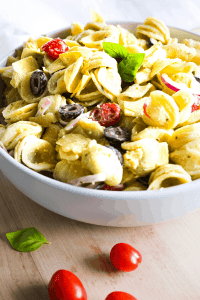 Front shot of bowl of creamy pesto pasta salad on wood surface with three grape tomatoes and a basil leaf.