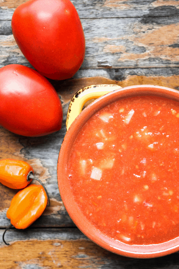 Top down shot of bowl of habanero salsa with two Roma tomatoes and two habaneros on a wood surface.