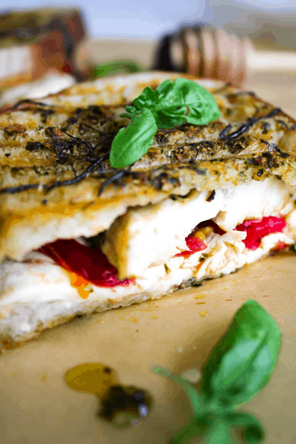 Close-up of chicken caprese panini topped with basil leaves.