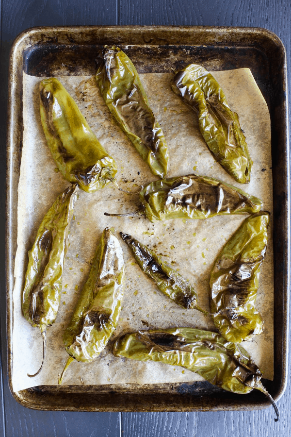 Top down shot of roasted hatch chiles on sheet pan lined with parchment paper.