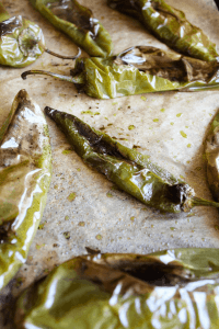 Roasted hatch chiles on a piece of parchment paper.