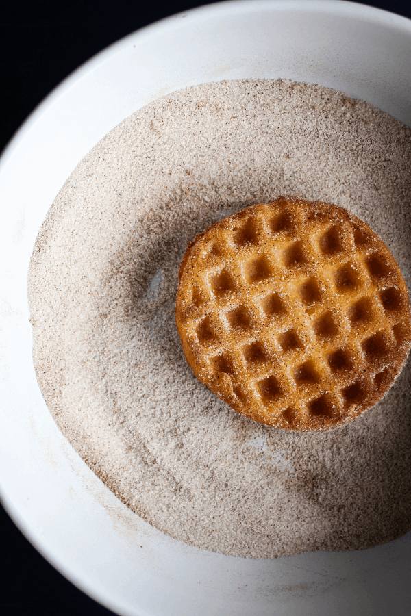 To down shot of a deep fried waffle in a bowl of cinnamon sugar.
