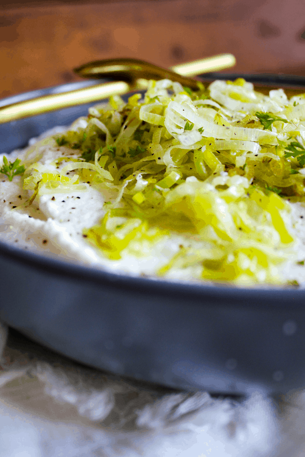 Bowl of mashed cauliflower with sautéed leeks with a spoon set across the top.