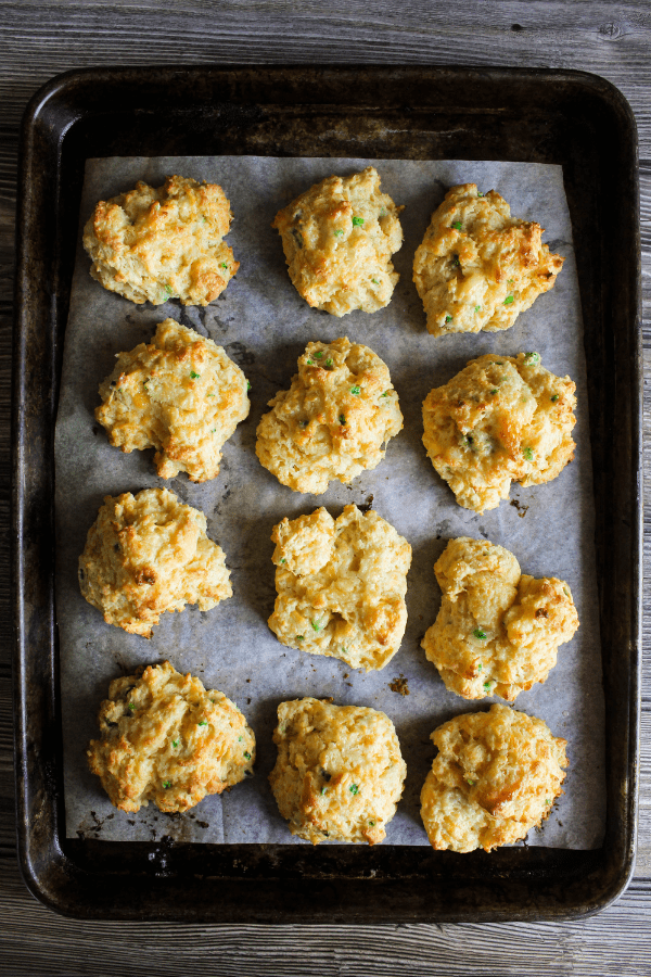 Top down shot of cooked biscuits on a baking sheet lined with parchment paper.