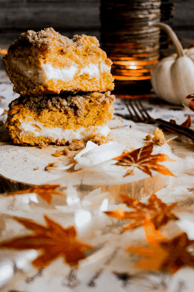Two slices of cake stacked atop each on a wood platter with fall decorations.