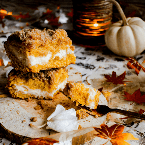 Two slices of pumpkin coffee cake on wood platter with a fork and fall decorations.