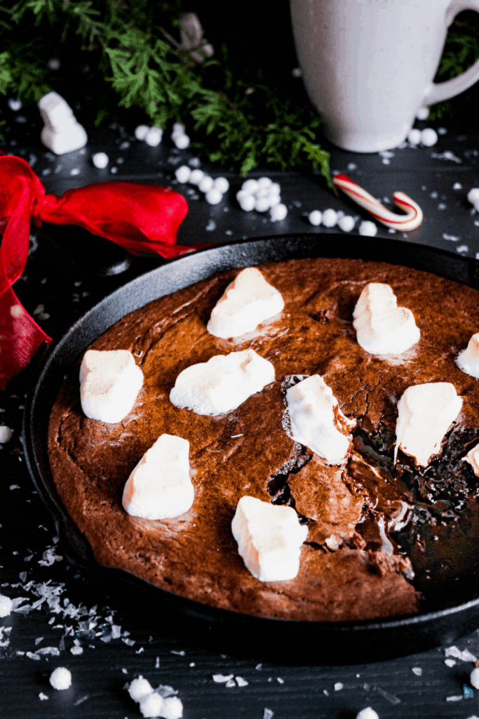 Skillet of hot cocoa brownies with holiday decorations and cup of cocoa.
