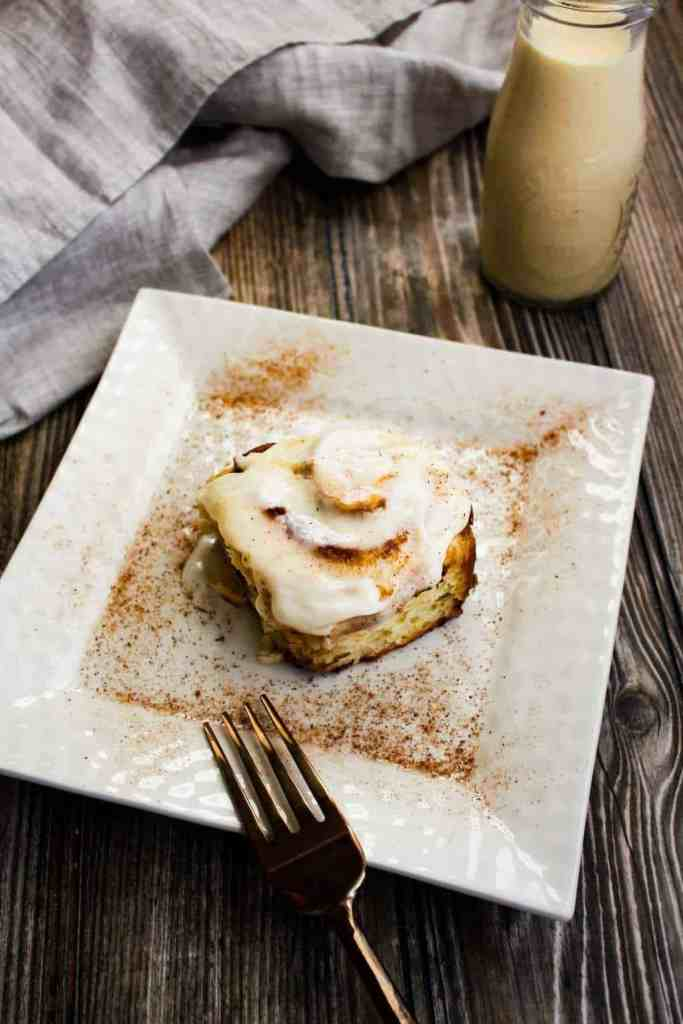 Eggnog cinnamon roll on cream plate with fork and a glass of eggnog in background.