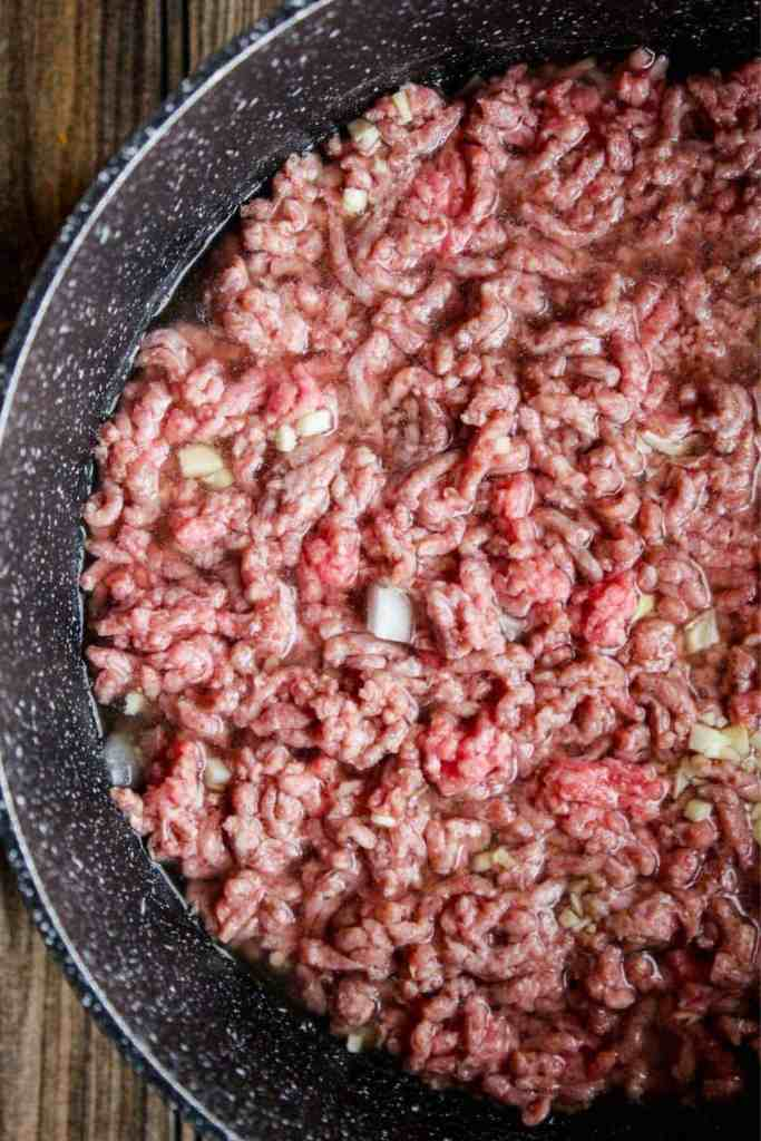 Ground beef, onion, garlic, salt, and chicken broth in a pot.
