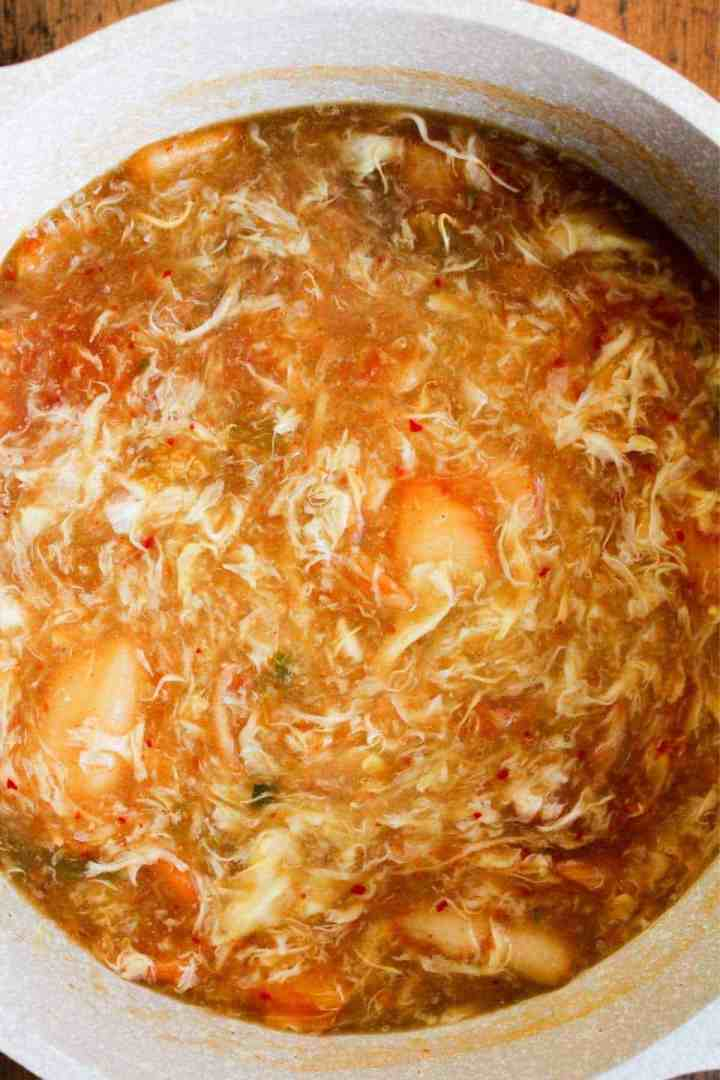 Miso egg drop soup with kimchi in a pot.