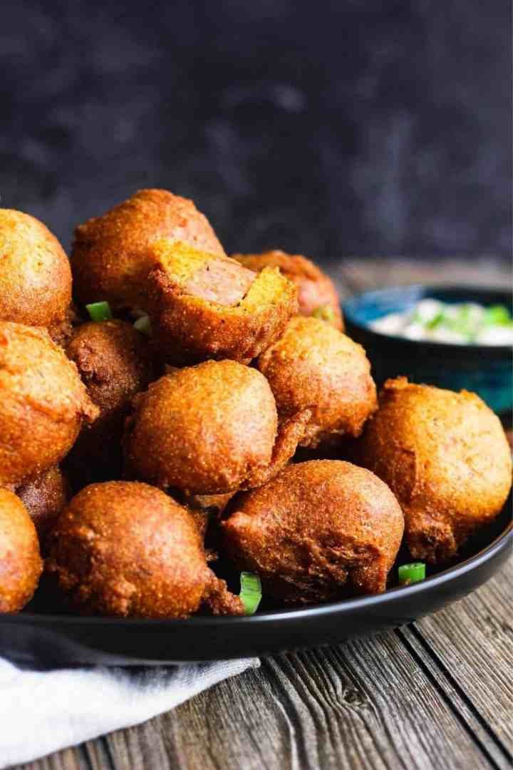 Plate of hush puppy corn dog bites with bowl of sauce.