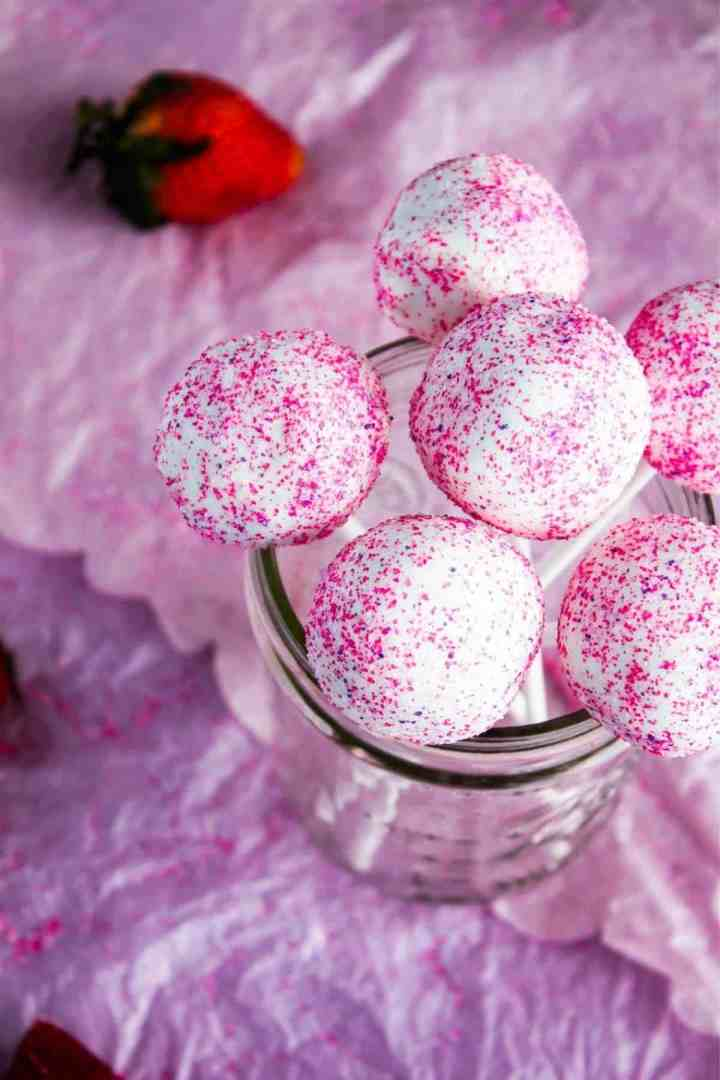 Glass jar filled with cake pops with scattered strawberries.