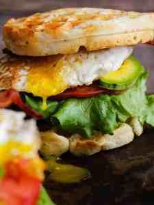 Breakfast waffle sandwich with egg yolk dripping.