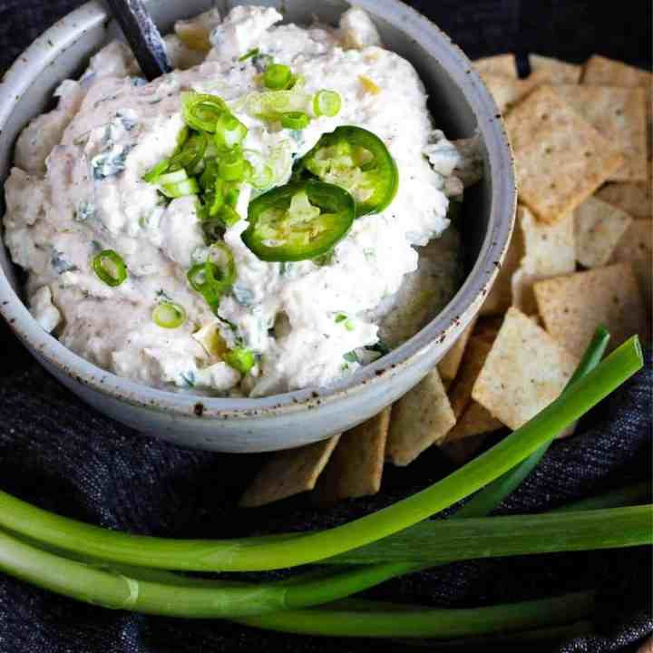 Bowl of jalapeno artichoke dip with crackers and green onion stalks.