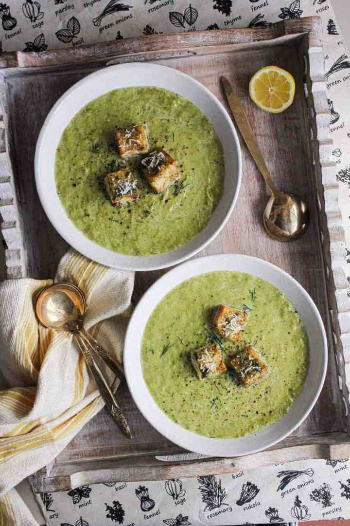 Two bowls of creamy asparagus soup on a tray with spoons and a kitchen towel.