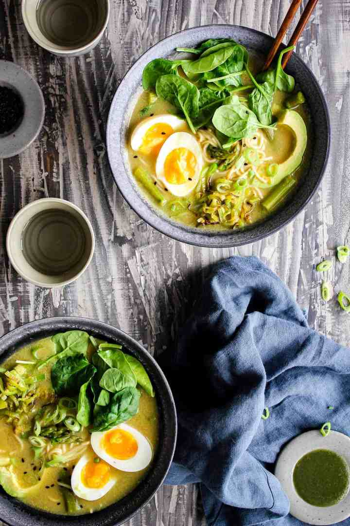 Two bowls of green goddess ramen with a blue towel and small bowls of condiments.