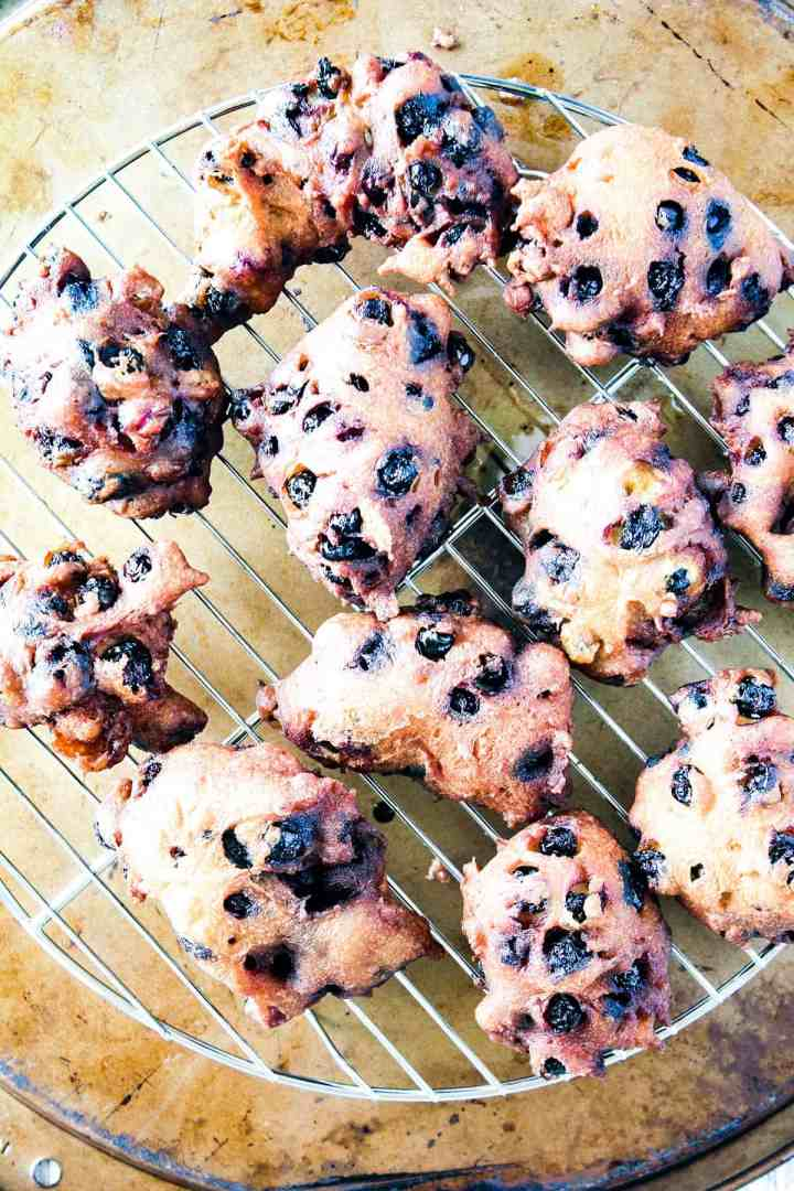 Fried blueberry fritters on a wire cooling rack.