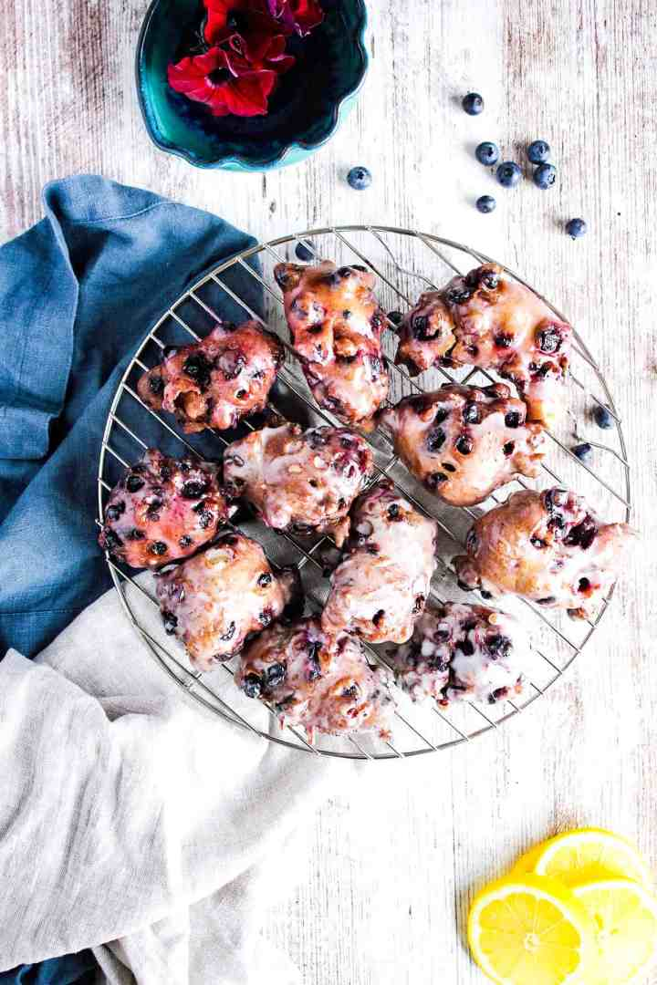 Wire cooling rack with berry fritters, scattered blueberries, and lemon slices.